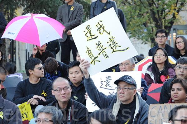 2014年10月1日晚,數百名卡爾加里市民在奧林匹克廣場舉行集會,支持香港太陽傘革命。圖為一位市民打出要求真普選的標語。(吳偉林/大紀元)