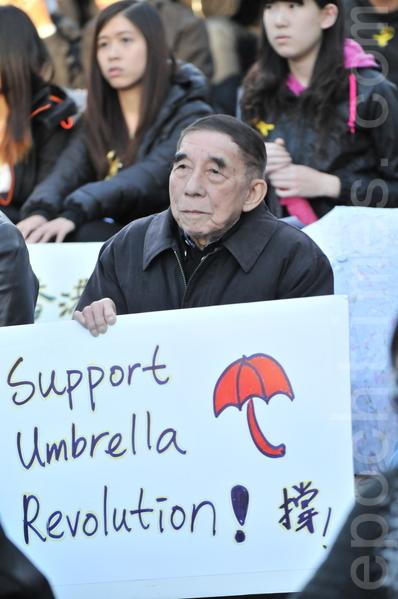 2014年10月1日晚,數百名卡爾加里市民在奧林匹克廣場舉行集會,支持香港太陽傘革命。圖為一位老者打出支持香港太陽傘革命的標語。(吳偉林/大紀元)
