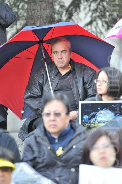 2014年10月1日晚,數百名卡爾加里市民在奧林匹克廣場舉行集會,支持香港太陽傘革命。圖為外籍人士帶著太陽傘,參加了當天的集會。(吳偉林/大紀元)