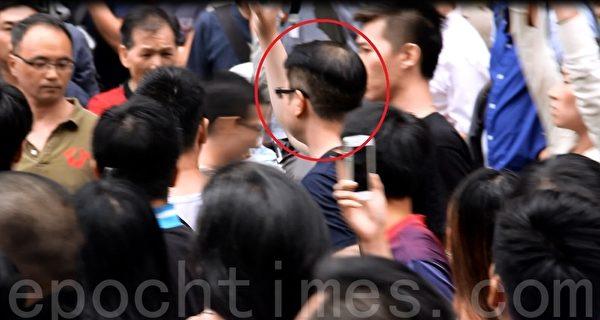紅圈中的「反佔中」人士舉起手作勢打經過他身邊的學生。(胡思仁/大紀元)