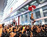 雨傘革命第六日,大批疑似黑社會成員到旺角集會現場多番挑釁滋事。有示威者爬至高處打開雨傘,以示對學生的支持。(孫青天/大紀元)