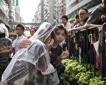 受疑似黑幫分子為主的「反佔中」人群的粗暴言行所驚嚇,參加和平請願活動的女學生趴在同伴身上失聲痛哭。(Philippe Lopez/AFP)