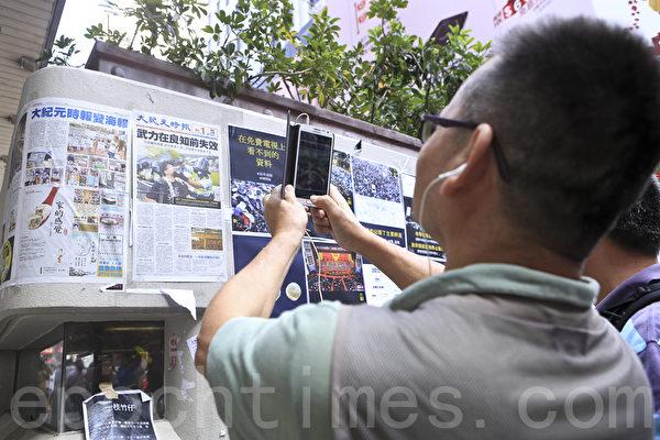 《大纪元时报》在香港雨伞运动期间,详实、客观的报导备受市民欢迎。图为2014年10月6日,香港街头不少市民驻足观看张贴的大纪元时报。(余钢/大纪元)