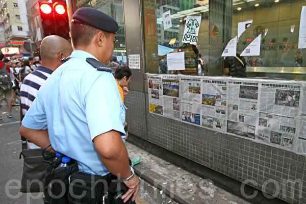 《大纪元时报》在香港雨伞运动期间,详实、客观的报导备受市民欢迎。图为2014年10月6日,在旺角占领区集会,警察驻足观看张贴的大纪元时报。(潘在殊/大纪元)