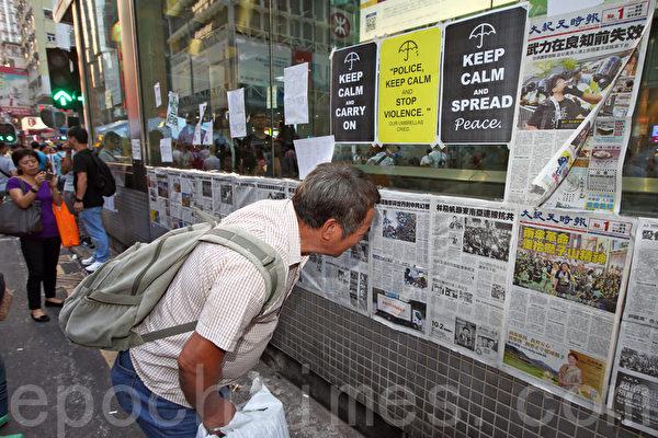 《大纪元时报》在香港雨伞运动期间,详实、客观的报导备受市民欢迎。图为2014年10月6日,在旺角占领区集会,不少市民驻足观看张贴的大纪元时报。(潘在殊/大纪元)