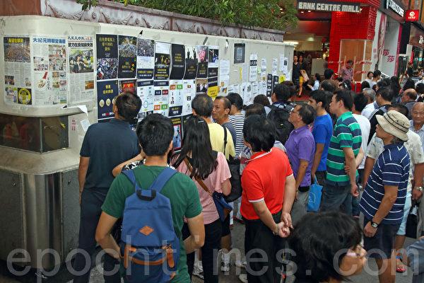 《大纪元时报》的记者团队,在香港雨伞运动期间,详实、客观的报导备受市民欢迎。图为2014年10月6日,在旺角占领区集会,不少市民驻足观看张贴的大纪元时报。(潘在殊/大纪元)