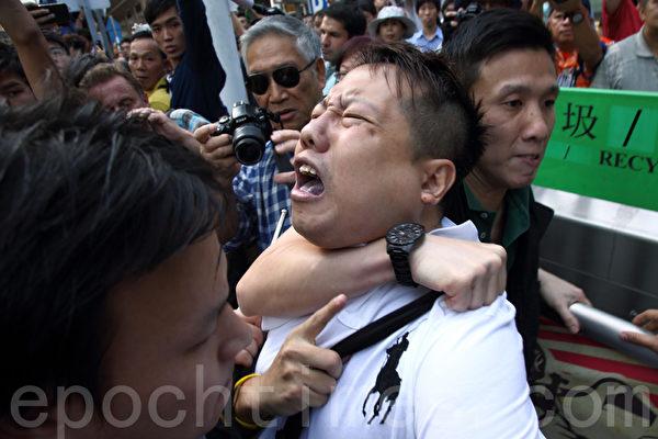 """中共策划的反占中者10月13日移除金钟道部分雨伞运动的3路障后,不少雨伞运动人士重新加固路障,但随即被便衣警察喝止,反问他们""""是否黑社会"""",并用警棍武力拘捕一名雨伞运动,一度引发在场的市民与警方对峙。(潘在殊/大纪元)"""