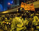 9月28日,香港警方首次在學生罷課、和平「佔中」期間動用武力驅散請願的市民。在現場,全副武裝的警察高舉橙色「速離否則開槍」橫幅。大紀元獲悉,作為中共江澤民集團在香港的代理人,梁振英當天真的就部署了真槍實彈的防暴隊到場,準備開槍鎮壓。(Bill/大紀元)