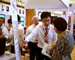 為躲避有毒食品和空氣污染,越來越多的中國人想到移民美國。圖為今年5月北京舉辦的一次國際房地產投資展中,一家美國房地產投資公司的代表向一位中國婦女做講解。(WANG ZHAO/AFP/Getty Images)