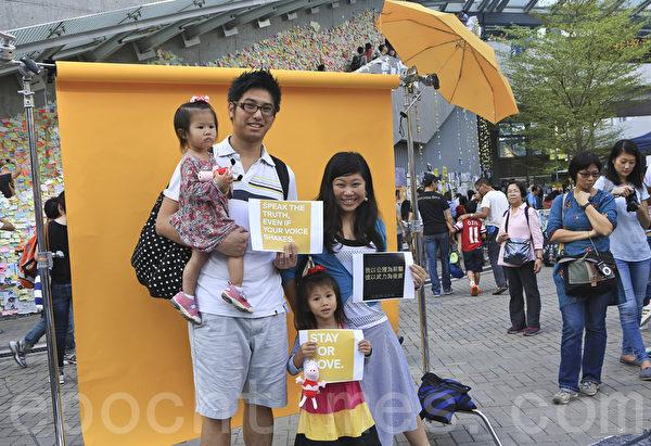 雨傘運動第22日,在金鐘的佔領現場一家四口影相留念。(余鋼/大纪元)