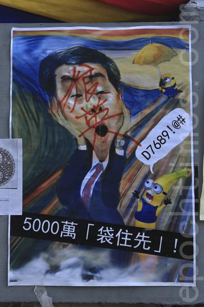 在金鐘的佔領現場市民用各種標語,漫畫表達對梁振英的不滿,圖為諷刺梁振英收取5000完賄款的漫畫。(余鋼/大纪元)