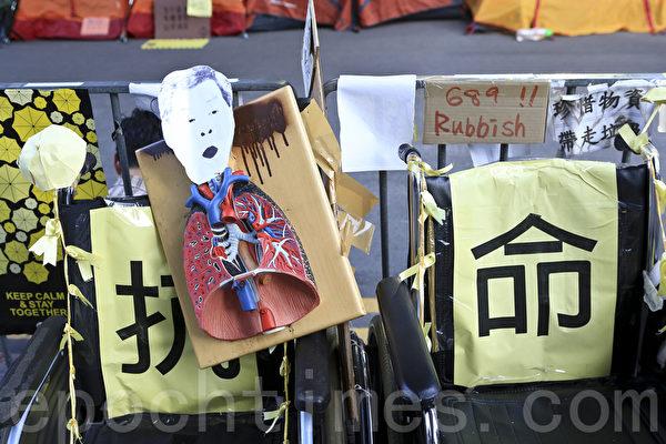 在金鐘的佔領現場市民用各種標語,漫畫表達對梁振英的不滿,圖為市民抗命梁振英政府的政改決定。(余鋼/大纪元)