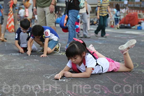 2014年10月19,孩子們為連日來駐守在廣場的哥哥姐姐們送上心意和祝福。(唐詩韻/大紀元)