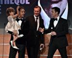 马修•麦康纳抱着女儿维达上台领奖,右为主持人吉米•金梅尔。(Kevin Winter/Getty Images)