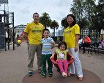 身著法輪大法T恤衫的馬克‧提克納與妻子瀟瀟帶著兩個孩子在舊金山市中心廣場的一個兒童遊樂場合影(唐風/大紀元)