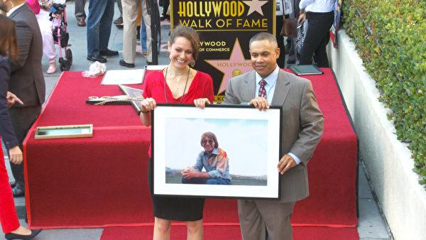 约翰•丹佛的儿子查克•多伊琴多夫和女儿杰西•贝尔•丹佛在授星仪式上手举父亲的照片。(杨阳/大纪元)