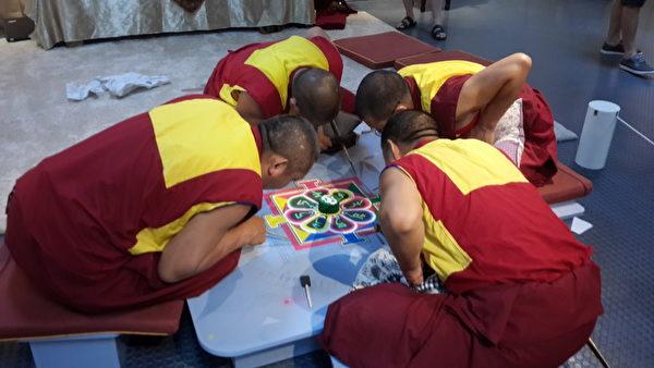 僧侣在现场展示坛城沙画创作。(林宝云/大纪元)