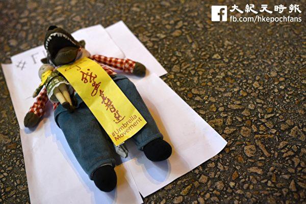 許多市民及學生惡搞諷刺梁振英,把「我要真普選」靈符貼在路母西公仔(梁振英)上,以表達香港人的心聲。(文瀚林/大紀元)