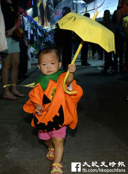 萬聖節的晚上,香港雨傘運動佔領區內有小朋友穿上南瓜服飾撐傘。(宋祥龍/大紀元)