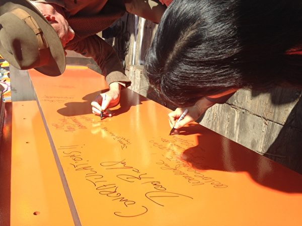 跨湾交通中心设计师(右)在首批地面工程钢梁上签名留念。(李兰/大纪元)