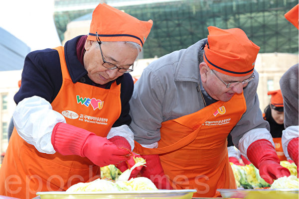 為期3天的「2014首爾泡菜文化節」於11月16日落下帷幕,這也是韓國歷屆規模最大的泡菜慶典。圖為韓國著名演員李順載(左)與外國人一起現場製作泡菜。(全宇/大紀元)