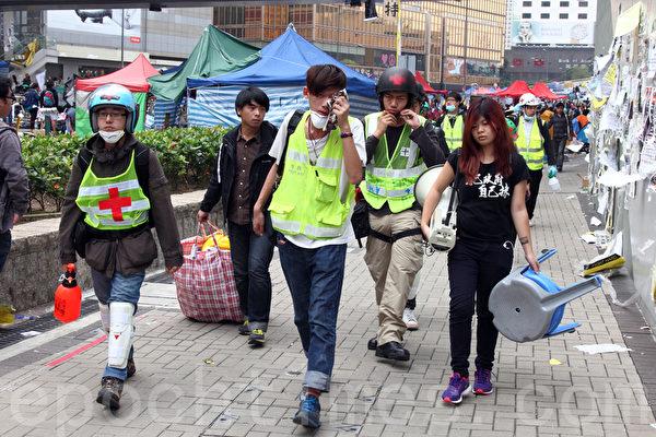 2014年12月11日,在禁制令清场后,香港警方出动大批警力对金钟雨伞广场进行全面的清场,有学生清场前撤离。(潘在殊/大纪元)