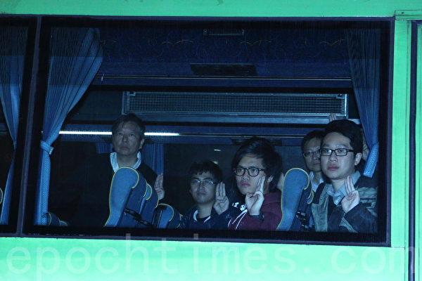 2014年12月11日,在禁制令清场后,香港警方出动大批警力对金钟雨伞广场进行全面的清场,学联秘书长周永康和立法会议员李卓人被捕后在巴士上做出电影《饥饿游戏》中的自由手势。(蔡雯文/大纪元)