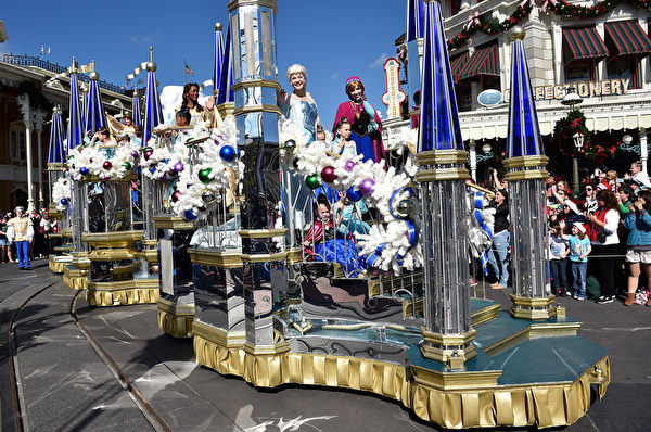 2014年12月9日,美國奧蘭多迪士尼樂園日前舉行花車遊行,《冰雪奇緣》的艾莎女皇和安娜公主與小影迷一起慶祝聖誕。(Mark Ashman/Disney Parks via Getty Image)
