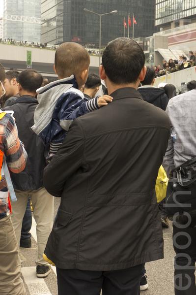 一位不愿露面的大陆人士抱着儿子到金钟雨伞广场直言香港有希望。(林怡/大纪元)
