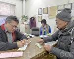 12月31日,谭先生(右)手中拿着50元到纽约中华公所捐款。(摄影:蔡溶/大纪元)