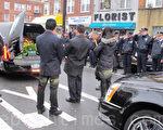 刘文健妻子手捧刘文健遗像、手持高香向灵柩鞠躬,在场警察敬礼。(林丹/大纪元)