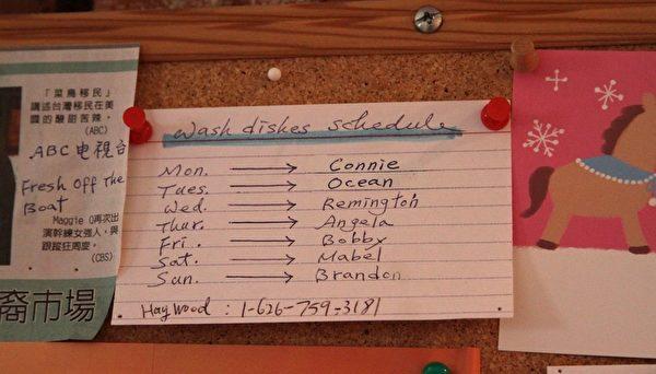 這是掛在周美麗家廚房旁邊墻上的洗碗值日表。四個學生和周美麗的三個孩子每週一人負責洗碗一天。(曾妮/大紀元)