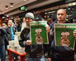 在柏林一家报亭里,两名男子有幸拿到了《查理周刊》。 (Carsten Koall/Getty Images)