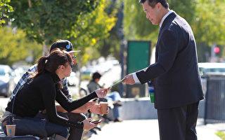 当时的加州参议员及旧金山市长候选人余胤良(右)在向公园里的民众发送竞选传单,摄于2011年11月7日。(by Justin Sullivan/Getty)