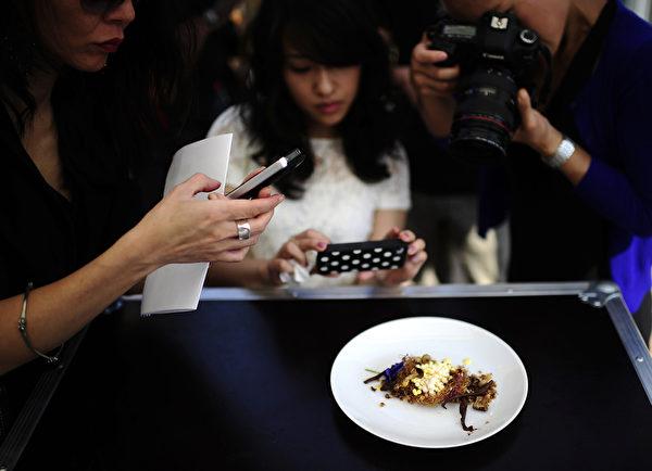 紐約國際飲食節期間,遊客正圍繞一道法式菜拍照。(EMMANUEL DUNAND/AFP/Getty Images)