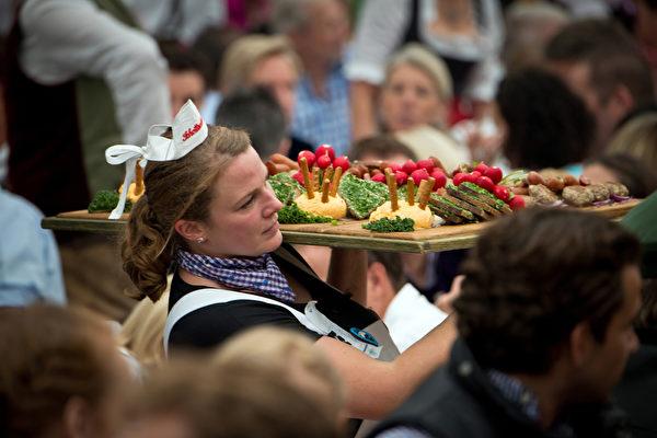 德國慕尼黑的國際啤酒節期間,侍者正端上巴伐利亞特色美食。啤酒節活動每年都會吸引幾百萬遊客。(Joerg Koch/Getty Images)
