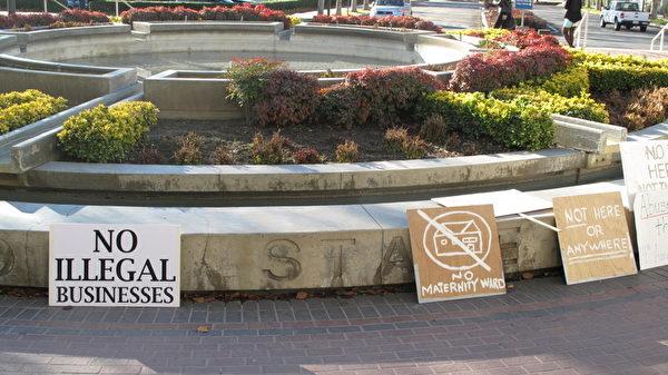 2013年1月,加州庫卡蒙加農場市反對月子中心的居民將抗議牌放在法庭外。(劉菲/大紀元)