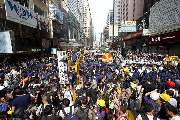 香港警方26日協助執達吏執行旺角亞皆老街至登打士街的一段彌敦道的禁制令,拘捕30多名示威者包括學聯副秘書長岑敖暉及學民思潮黃之鋒等人。(潘在殊/大紀元)