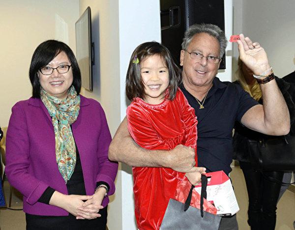 Experience Auto Group 总裁斯图尔特• 哈亚穆(右)与时尚Elite杂志发行人Ellen Wang(左)为来宾抽奖,一个小女孩抽中奖品非常开心。(Andy Chen/大纪元)
