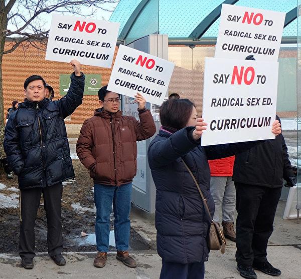 """数百人次的华裔家长于3月12日到士嘉堡爱静阁中学(Agincourt C.I.)大门口集会,抗议省府即将实施的性教育大纲。他们数百次高喊""""我们反对""""口号。集会至少持续了2小时。(周月谛/大纪元)"""