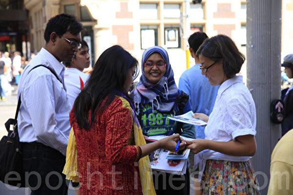 2014年3月22日星期六,在悉尼市中心喬治大街舉辦了悉尼聲援1億6千萬中國人「三退」的集會活動,令在澳洲的民眾感到震驚。圖為他們在征簽表上簽名,制止中共活摘器官,反對迫害。(袁麗/大紀元)