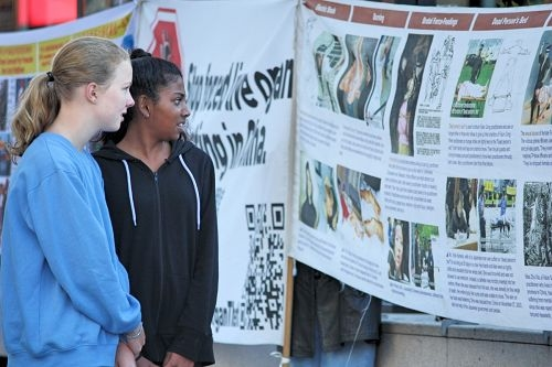 澳洲市民Sarah和Anika在法輪功真相橫幅面前一邊看著還一邊討論著,她們主動要廣傳中共活摘法輪功器官盜賣的真相,讓更多的人來簽名制止中共活摘器官的惡行。(明慧網)