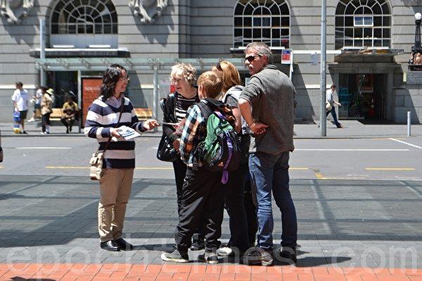 2014年11月8日中午,新西蘭法輪功學員在奧克蘭市中心舉辦反酷刑展示,譴責中共活摘法輪功學員器官牟利的暴行。法輪功學員向民衆講真相。(張莉莉/大紀元)