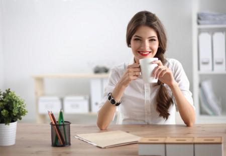 年轻商人坐在办公室的桌子拿著杯子喝水(fotolia)