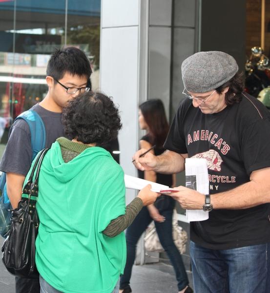 """摩托车商场员工杰克(Jake,右)签名反""""活摘""""。(明慧网)"""