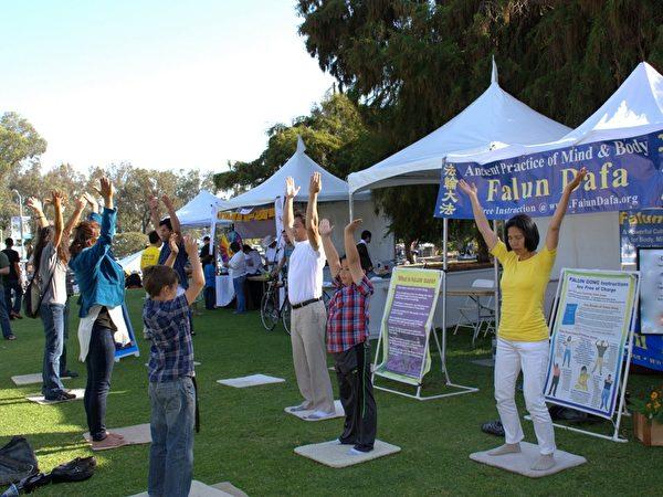 图:4月19日,加州圣地亚哥法轮功学员还参加了圣地亚哥地球日大型街市。图为民众(左排)和法轮功学员学功。(杨婕/大纪元)