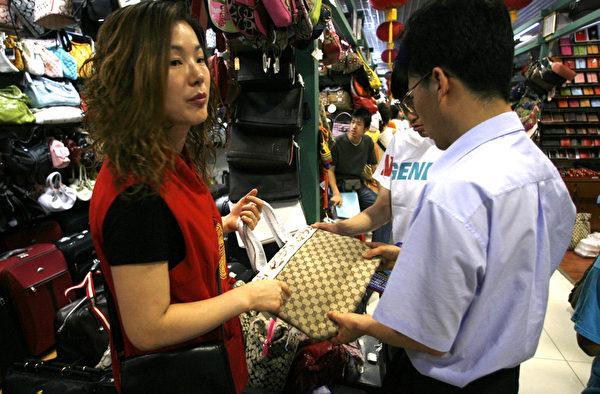 据统计,目前全球仿冒货品有九成来自中国和香港。图为假货充斥的北京秀水街市场,摊商正在兜售。(Peter PARKS/AFP)