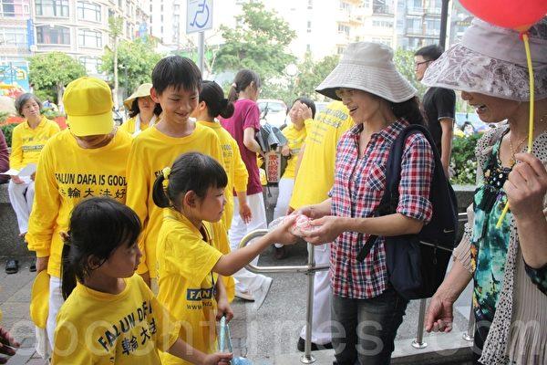 中区明慧学校纯真可爱的小弟子分送寿桃给现场民众和游客,共同分享修练法轮大法的喜悦。(黄淑贞/大纪元)