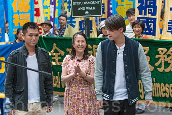 5月15日,8千法輪功學員在紐約聯合國附近集會聲援2億華人退出中共組織。圖為全球退黨服務中心主席易蓉(中)和兩個現場退黨的青年。(馬有志/大紀元)