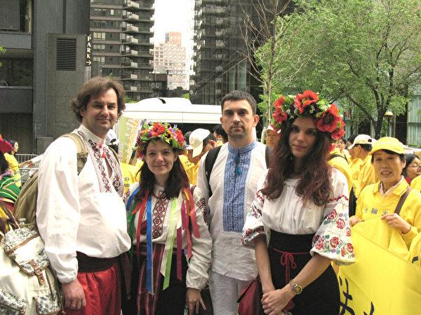 """2015年""""世界法轮大法日""""大游行开始前,来自乌克兰的部分法轮功学员在联合国总部前的小公园内合影。右一、右二分别为蒂蒂亚娜和阿尔乔姆。(张小清/大纪元)"""